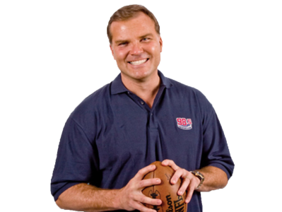 A cutout of Scott Zolak from the waist up holding a football and smiling at the camera.